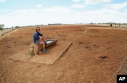 FILE - Farmer Andrew Higham looks over his parched land on his Gunnedah property in northwestern New South Wales, Australia.