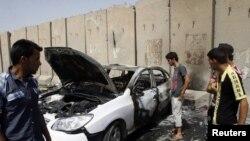 Warga Baghdad memeriksa lokasi ledakan di distrik Kazimiyah, Baghdad hari Sabtu (16/6). Serangan atas peziarah Syiah ini menewaskan 26 orang setelah serangan sebelumnya hari Rabu menewaskan 72 orang.
