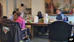 Rob Farley, a Washington Attorney and church member of a congregation, sits at the table with others. He starts early each day offering coffee and breakfast to the city homeless