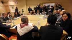 The Yemeni Houthi rebel delegation, background, and delegates of the internationally recognized Yemeni government, foreground, meet for a second day for talks on implementing a prisoner exchange agreed to in Sweden last month, in Amman, Jordan, Thursday, Jan. 17, 2019.