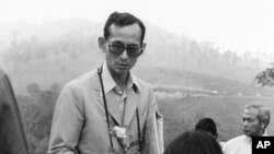 Thai King Bhumibol Adulyadej receives a small rose plant from a woman as he makes a visit to one of his crop substitution projects in Northern Thailand, Feb. 16, 1981.