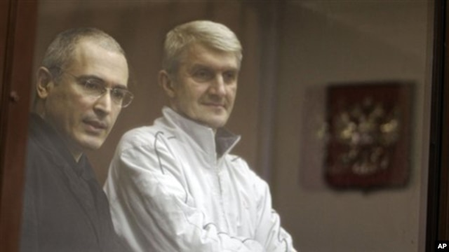 Former Yukos CEO Mikhail Khodorkovsky, left, and his co-defendant Platon Lebedev, right, stand behind a glass wall at a court in Moscow, Russia, (File)