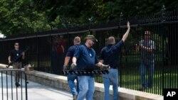 Des travailleurs installent une barrière dans l'enceinte de la clôture de la Maison Blanche après l'intrusion sans autorisation d'un homme, à Washington, 1er juillet 2015.