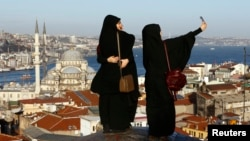 Young women take selfie photographs in front of the New Mosque by the Bosphorus strait in Istanbul, Turkey, Jan. 12, 2016. A Syrian suicide bomber is thought to be responsible for an attack which killed at least ten people including foreigners in the hear