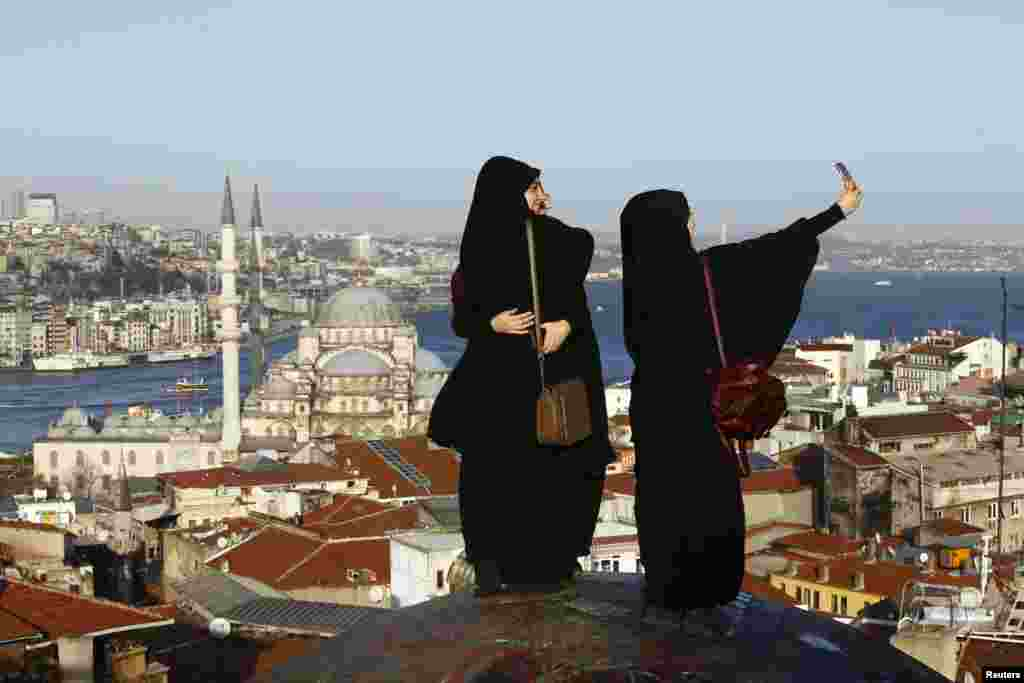 Young women take selfie photographs in front of the New Mosque by the Bosphorus strait in Istanbul, Turkey. A Syrian suicide bomber is thought to be responsible for an attack which killed at least ten people including foreigners in the heart of Istanbul's historic Sultanahmet tourist district on Tuesday.