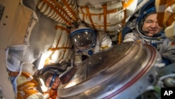 This photo provided by NASA shows NASA astronaut Jeff Williams, left, Russian cosmonaut Alexey Ovchinin of Roscosmos, center, and Russian cosmonaut Oleg Skripochka of Roscosmos inside the Soyuz TMA-20M spacecraft a few moments after they landed in a remote area near the town of Zhezkazgan, Kazakhstan on Wednesday, Sept. 7, 2016.