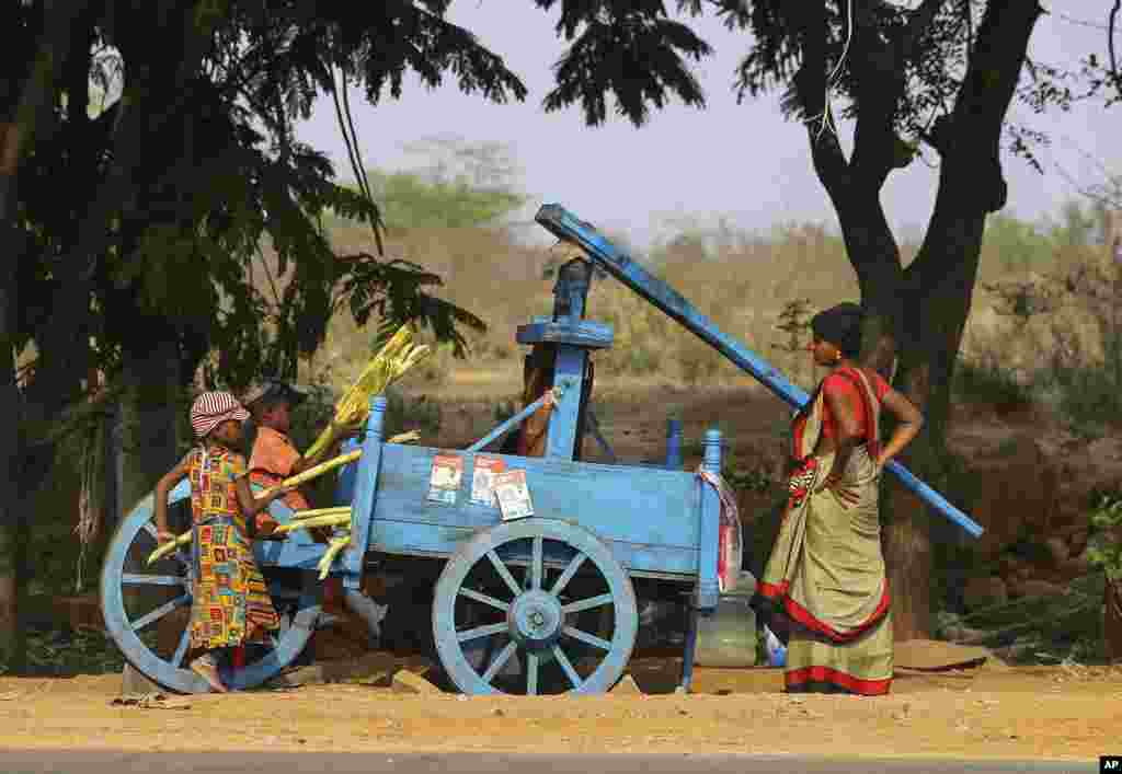 Children help a woman to extract juice from sugarcane to sell by a roadside on the outskirts of Hyderabad, India.
