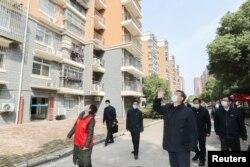 中国国家主席习近平在视察武汉一个居民区时向被隔离的居民招手致意。(2020年3月10日)