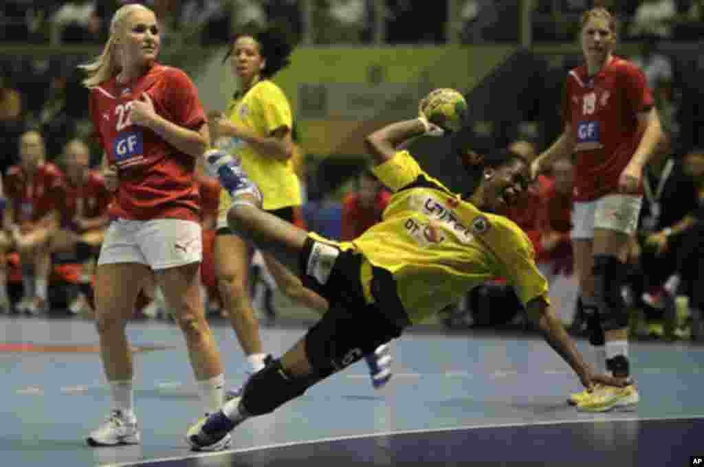 Angola's Madalena Calandula attempts to score as Denmark's players look on during their Women's World Handball Championship quarterfinal match in Sao Paulo December 14, 2011. REUTERS/Ricardo Moraes (BRAZIL - Tags: SPORT HANDBALL)