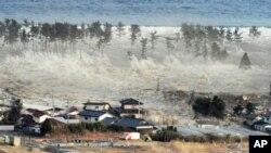 巨大的海啸涌向日本东北部的一个居民区