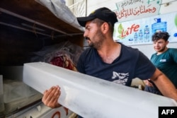 Seorang karyawan memasukkan balok es ke truk pick-up pelanggan di sebuah pabrik di kota Mosul, 3 Juli 2021. (AFP)