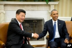 FILE - President Barack Obama shakes hands with Chinese President Xi Jinping during their meeting in the Oval Office of the White House in Washington, Sept. 25, 2015.