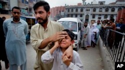A man helps an injured boy to a hospital after an earthquake hit Peshawar, Pakistan, April 10, 2016.