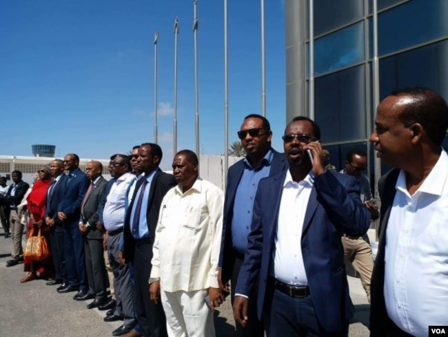 Somali officials line up at Mogadishu's airport to welcome Somali migrants from Libya, Feb. 17, 2018. (H.K. Qoyste/VOA)