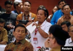 Bali bombing survivor Chusnul Khotimah stands behind Indonesia Chief Security Minister Wiranto as she speaks during a meeting between former militants and victims in Jakarta, Indonesia, Feb. 28, 2018.
