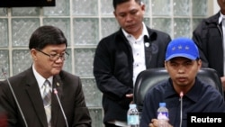 Jerry Umlang (R) answers questions from the members of the media regarding his alleged involvement in the kidnapping and murder of South Korean businessman Jee Ick-Joo while Department of Justice Secretary Vitaliano Aguirre (L) looks on during a press bri