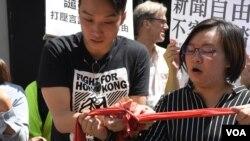 示威者剪爛象徵北京紅線的布條以示抗議。(美國之音湯惠芸拍攝)