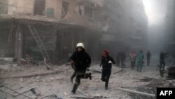 Emergency responders rush following a reported barrel bomb attack by government forces in the Al-Muasalat area in the northern Syrian city of Aleppo, Nov. 6, 2014.