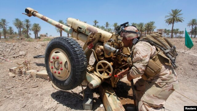 Iraqi security forces fire artillery during clashes with Sunni militant group Islamic State of Iraq and the Levant (ISIL) in Jurf al-Sakhar, June 14, 2014.
