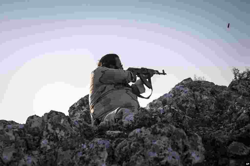 A Syrian opposition fighter aims at government forces in Telata village in Idlib province, Sept. 29. 2013.