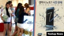 1일 서울 용산 전자상가 방문객들이 삼성전자 '갤럭시 노트7' 광고 옆에서 구매 상담을 하고 있다. 이날 삼성 측은 품질 점검을 위한 추사 검사가 진행되고 있어 해당 제품 출하가 지연되고 있다고 밝혔다.