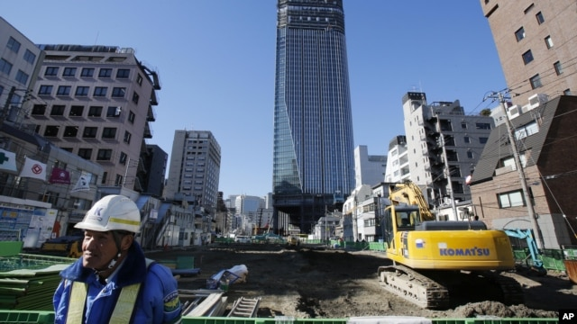 A security man stands by a road construction site in Tokyo. PM Shinzo Abe delivered a stimulus package of public works and other projects aimed at revitalizing the sagging economy, January 11, 2013.