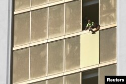 Workers board up a broken window at the Mandalay Bay Resort and Casino, where shooter Stephen Paddock conducted his mass shooting along the Las Vegas Strip, in Las Vegas, Nevada, Oct. 6, 2017.