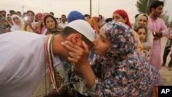 Seorang jemaah haji dari Srinagar, Kashmir, mendapat ciuman perpisahan dari kerabatnya sebelum pergi naik haji (10/8). (AP/Mukhtar Khan)