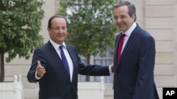 France's President Francois Hollande, left, welcomes Greece's Prime Minister Antonis Samaras at the Elysee Palace, Paris, August 25, 2012.