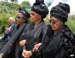 FILE - Winnie Madikizela-Mandela, right, Nelson Mandela's former wife, and Nelson Mandela's widow Graca Machel, centre, walk from the funeral service to the burial site of former South African President Nelson Mandela in Qunu, South Africa, Sunday, Dec. 15, 2013.