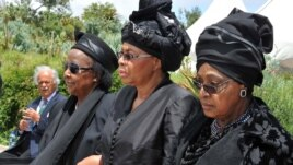 Winnie Madikizela-Mandela, right, Nelson Mandela's former wife, and Nelson Mandela's widow Graca Machel, centre, walk from the funeral service to the burial site of former South African President Nelson Mandela in Qunu, South Africa, Sunday, Dec. 15, 201