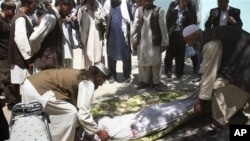 Relatives wrap the body of a civilian, who was killed during a clash of militants with policemen in Ghazni, southwest of Kabul, Afghanistan, May 1, 2011