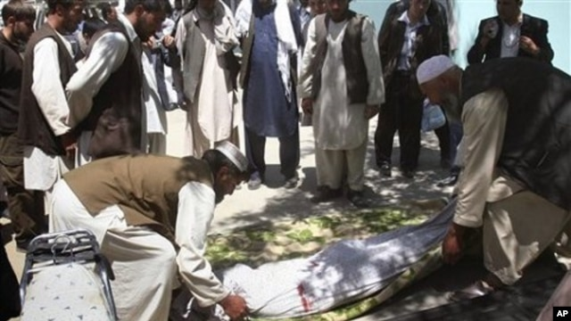 FILE - Relatives wrap the body of a civilian, who was killed during a clash of militants with policemen in Ghazni, southwest of Kabul, Afghanistan.