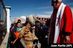Pastor Sebastian Obermaier memberkati seekor anjing dengan air suci selama Hari Anjing, setelah merayakan Misa di El Alto, Bolivia, Sabtu, 16 Agustus 2014. (Foto: AP/Juan Karita)