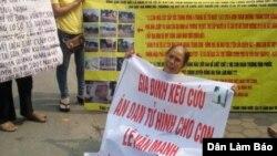 Bà Nguyễn Thị Việt, mẹ của tử tù Lê Văn Mạnh, cầm biểu ngữ kêu cứu cho con.