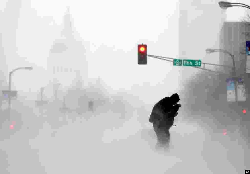 Một khách bộ hành đang cố băng qua đường giữa cơn bão tuyết ở St. Louis, tiểu bang Missouri, Hoa Kỳ.
