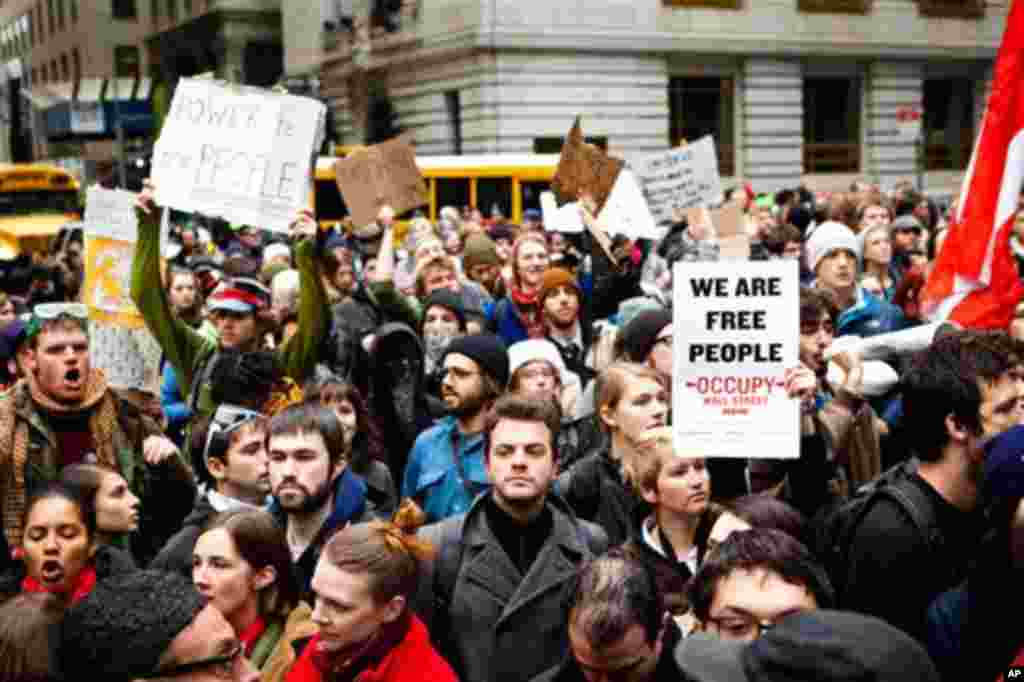 Демонстранти во Долен Менхетен, во обид да се пробијат до Њујоршката берза. Полицијате претходно ја огради локацијата. (AP Photo/John Minchillo)