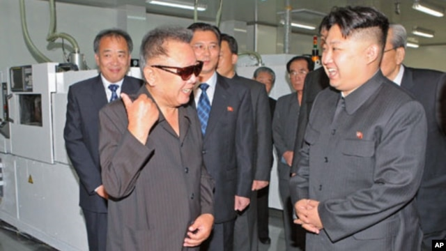 North Korean leader Kim Jong Il (front L) and his son Kim Jong-un (R) talk as they visit Mokran Video Company in Pyongyang, in this undated picture released September 11, 2011.