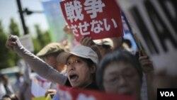 """數以百計的群眾在日本首相府外面示威,反對解禁集體自衛權新安保法的相關法案,他們舉著的標語牌上寫著""""不要戰爭""""(2015年5月14日)"""