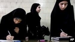 Des étudiantes iraniennes remplissant des formulaires d'inscription indiquant leur volonté pour le martyre, ou pour mener des attaques suicide, à Téhéran, en Iran, le 18 février 2006.