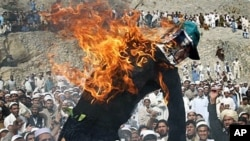 Effigy of the American pastor Terry Jones is seen burning during a demonstration in Shinwar, Nangarhar province, east of Kabul, Afghanistan, after protests erupted in Afghanistan again Monday against the Florida pastor's burning of the Quran, April 4, 201