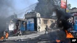 在海地首都太子港,被抗議者點燃的輪胎在街頭熊熊燃燒,警察正試圖撲滅火焰。(2021年7月14日)