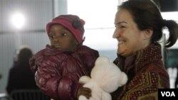 Seorang ibu warga Perancis menggendong anak adopsinya dari Haiti di bandara Roissy, Paris.