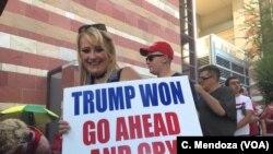 Một phụ nữ xếp hàng chờ vào hội trường nơi TT Trump sẽ phát biểu trong một cuộc tập họp tương tự như lúc còn vận động tranh cử. Ảnh chụp ngày 22/8/2017.