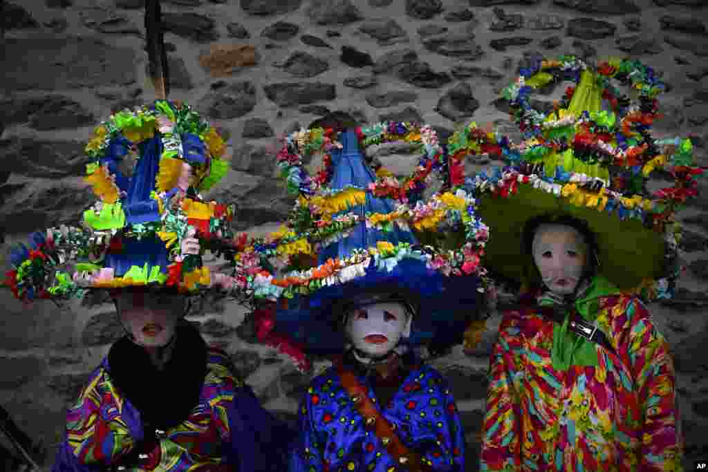 A group of participants dressed in traditional clothes and wearing large hats decorated with ribbons and feathers, known as ''Ttutturo'', take part in the Carnival of the Pyrenees villages of Leitza, northern Spain, Jan. 30, 2018.
