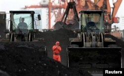 FILE - An employee walks between front-end loaders which are used to move coal imported from North Korea at Dandong port in the Chinese border city of Dandong, Dec. 7, 2010.