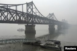 Trucks move across the bridge linking North Korea with the Chinese border city of Dandong in this March 3, 2016 file photo.