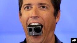 El CEO de GoPro, Nick Woodman, sostiene una cámara GoPro con su boca.