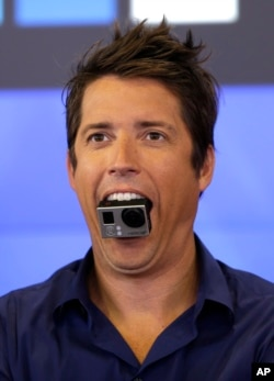 GoPro's CEO Nick Woodman holds a GoPro camera in his mouth as he celebrates his company's IPO