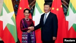 Myanmar State Counselor Aung San Suu Kyi, left, and Chinese Premier Xi Jinping pose for the media before a meeting in Beijing, Aug. 19, 2016.